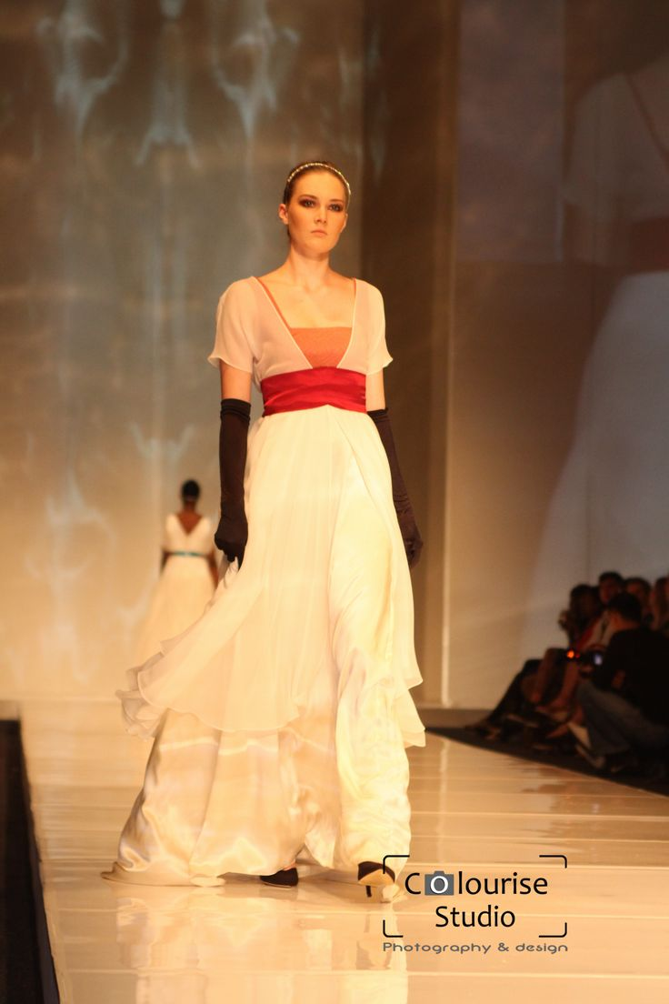 A gown of ivory silk satin with silk chiffon and then silk georgette overlays on the skirt set to different lengths.The sleeves are also of silk georgette over a bodice made from the panel of an antique silk kimono panel. It features a wine red silk satin sash.