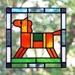 かわいらしい仔馬モチーフのステンドグラス ミニパネルです。玄関やリビング、ベッドルームなど、どんな場所にもなじみます。パネル上部には吊り下げ用の金具が付いていますので、お手持ちのチェーンや紐で吊り下げて飾ることができます。陽のあたる窓際に吊り下げると、ガラスの色が鮮やかに(濃く)浮き上がり、とてもきれいです。お好みで飾る向きを変えていただけます。作品は自立しませんが、壁に立てかけたりお手持ちの皿立てに立てかけて飾ることも可能です。その場合は倒れて割れないよう布などを敷くことをお勧めします。 リビングボードの上や、飾り小窓、出窓などに飾っても素敵です。DIYが得意な方は、ドアや壁にはめこんたり額に入れて飾ってみてはいかがでしょうか。大きさ:たて約15cm×よこ約15cm×厚さ約3mm 重さ:約200g 素材:ガラス、鉛●ご購入の前に必ずご確認ください。作品はすべてハンドメイドの一点ものです。 ガラス作品のため、光のあたり具合によって色の見え方や透明感が違ってきます。…