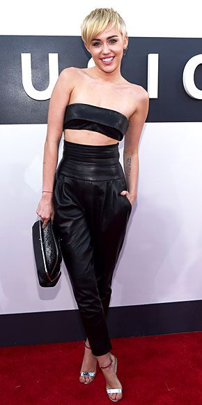 MILEY CYRUS No hair knots this year? Miley Cyrus goes surprisingly simple in a black leather bandeau top and high-waisted pants, which we imagine is her version of a classic suit.