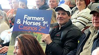 Horseman Paul MacKenzie holds a Farmers and Horses 1st sign supporting horse racing industry at Hamilton casino meeting. (Samantha Craggs/CBC)