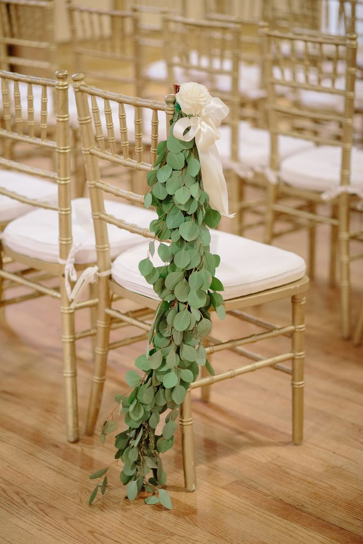 Leafy chair decor, natural indoor wedding ceremony, gold chairs, cream silk ribbons // Riverland Studios
