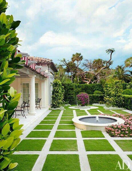 Spanish Colonial Revival terrace with squares of lawn and a round fountain.