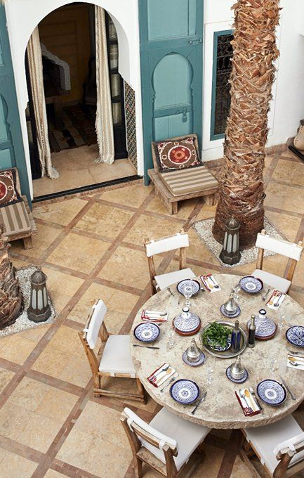 Ryad Dyor Marrakech, Morocco. Screen doors, tiles inside door frame, low chairs with those pillows, easy patio pattern, dishes