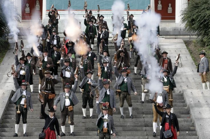 """Bavarian riflemen and women fire their muzzle loaders in front of the """"Bavaria"""" statue at the 183rd Oktoberfest beer festival,  Munich."""