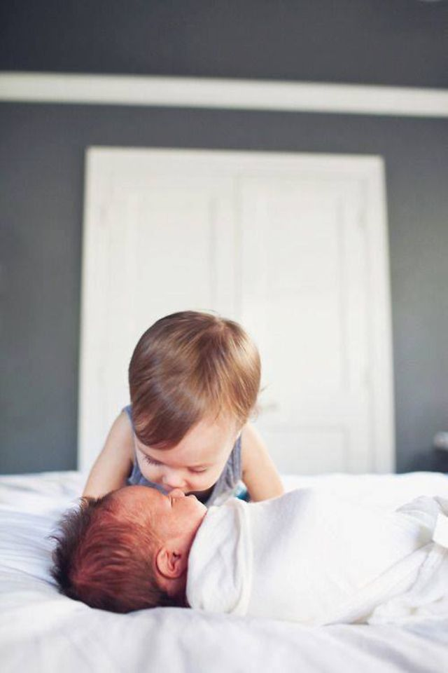 baby loving on new baby - I should try to get a picture like this, they're both so tiny!