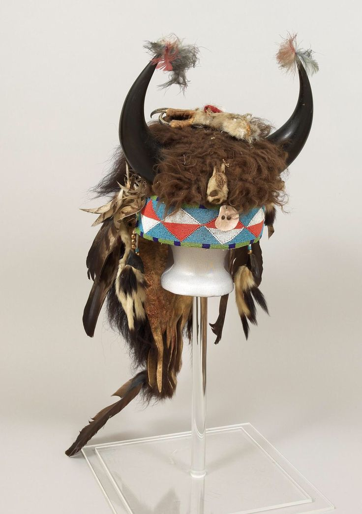 Headdress, Plateau. ДА2..Date: ca. 1905.  Dimensions: width at horns: 13 in, L: 32 in.  Buffalo headdress - felt liner; buffalo horns and fur; beaded brow band with diamond pattern in orange and white on blue ground, green and blue border; abalone shell and bobcat foot in front; eagles foot on top; mink hide in back; short buffalo fur trailer with hawk feathers along sides; dew claws and ermine tails at ends of brow band. Buffalo dancers headdress. Buffalo Bill Center of West.