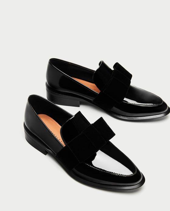 Zapato plano color negro. Detalle de lazo de terciopelo en el empeine.