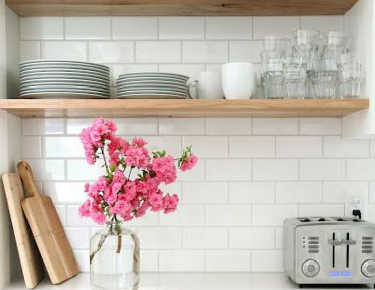 Simple kitchen design. White kitchen, white gloss subway tile, pink flowers, silver toaster.