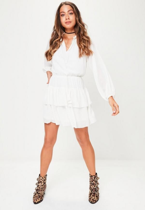 White skater dress featuring a high ruffled neck, long sleeve, elasticated drop hem and frill details.