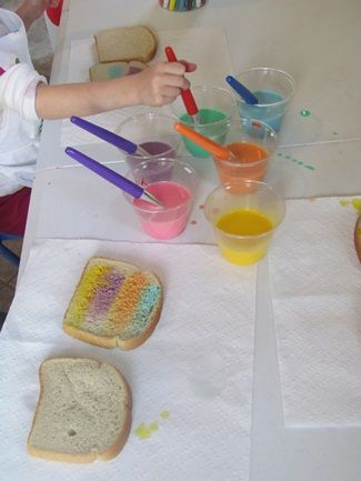 Rainbow Toast - pretty and tasty too! Food colouring in milk, with new paint brushes (of course!), painted onto bread before toasting. The Nursery children enjoyed making their own snack!