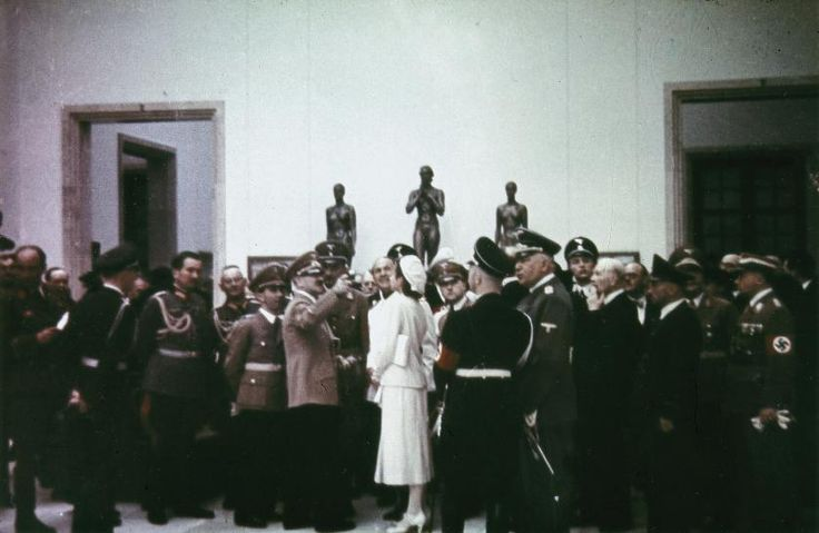 Photograph by Heinrich Hoffmann of Gerdy Troost speaking with Hitler and surrounded by a crowd of Nazi bigwigs at the House of German Art in Munich on the Day of German Art, July 16, 1939. Those pictured (from left to right): Eugen von Schobert, Joseph Goebbels, Adolf Hitler, Dino Alfieri, Gerdy Troost, Heinrich Himmler (back turned), Konstantin von Neurath.