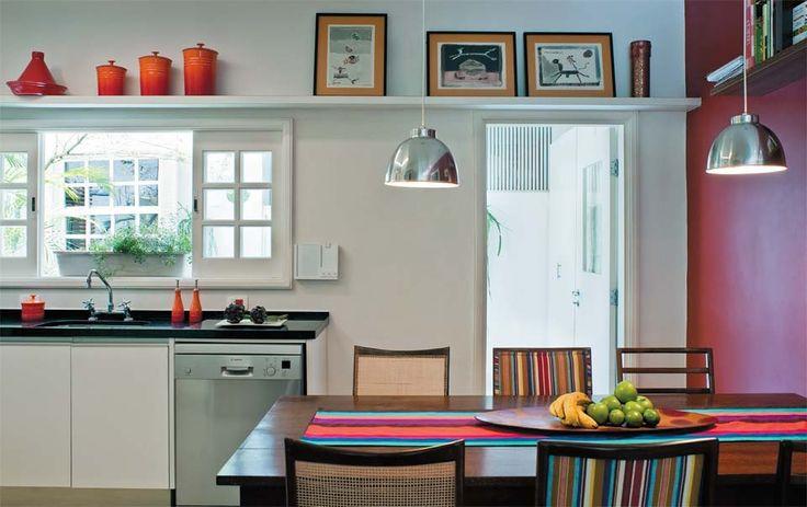 A atmosfera calorosa da cozinha vem da tonalidade quente numa das paredes e da luz pontual dos pendentes. Bancada de granito preto (Pedra de Esquina) e marcenaria da Florense. de madeira a janela recuperada com uma demo de tinta branca.