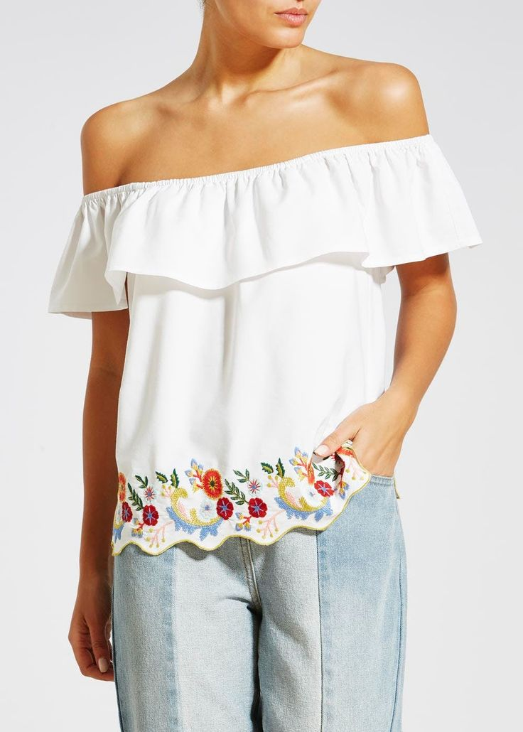 White bardot top featuring floral embroidery at the scalloped hemline.