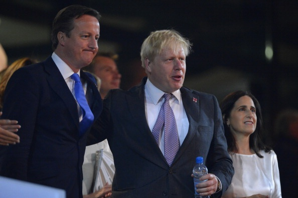Britain's Prime Minister David Cameron (L) stands next to London's Mayor Boris Johnson (C) and Marina Wheeler (R) during the opening ceremony of the London 2012 Olympic Games on July 27, 2012 at the Olympic Stadium in London