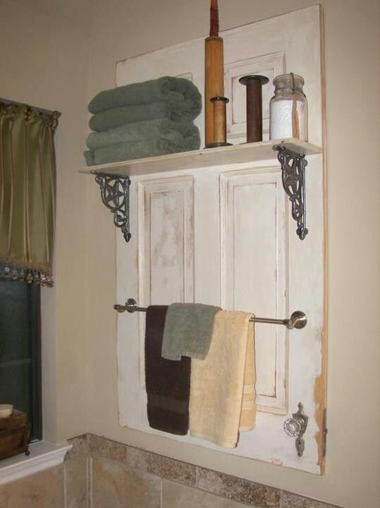 bathroom storage....rails nailed to old cabinet door...less holes in the wall