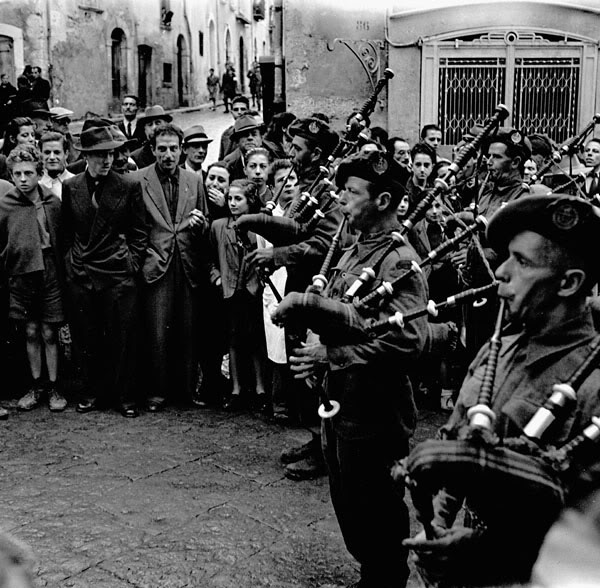Pipers of the 48th Highlanders of Canada, playing in the streets of Campobasso, Italy, 18 October 1943