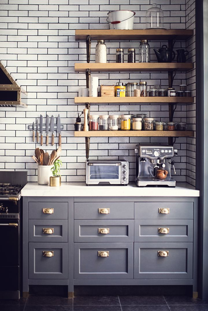 open shelving, white subway tile with dark grout, light counter, dark shaker style lower cabinets, hardware