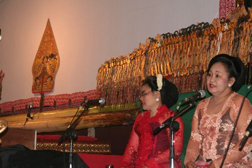This is another side of a stage. Two women in this picture are sinden or Javanese traditional singers. Behind them, there are hundreds of puppets and Gunungan. #javanese #singer #art #puppet #siluette #performance #tradition