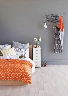 I soveværelset her er der skejet ud med mønstre og farver i tekstilerne, mens rammerne for rummet er holdt i rolige toner med en grå nuance på væggen og et lyst trægulv, som giver en god base for at eksperimentere med farver i sengetøj og sengetæpper.