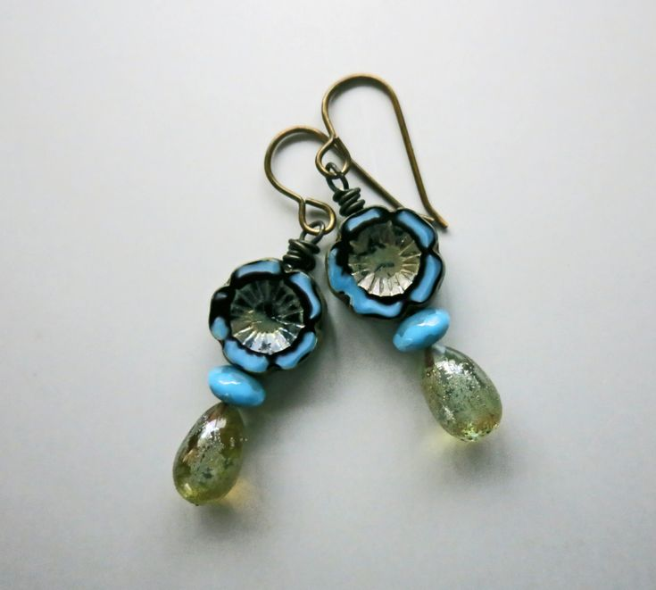 "These pretty earrings make me think of turquoise flowers gratefully soaking up a rain shower.  Handmade lampwork glass in teardrop shapes remind me of raindrops. Czech glass flowers and turquoise pressed glass beads sit atop the translucent ""raindrops"", which have just a hint of a golden hue."