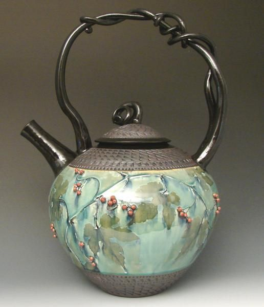 Beautiful light green enameled tea pot with berries and vines.