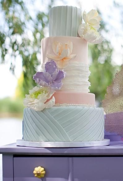 Pastel blue and peach wedding cake-I really like how each layer is different.  Very pretty.