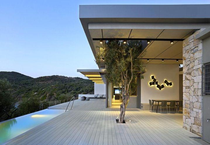 Incorpora con naturalezza un albero di ulivo la terrazza panoramica che amplia il living dell'abitazione di vacanza progettata in Grecia da Z-Level. Piscina a sfioro protesa verso il panorama