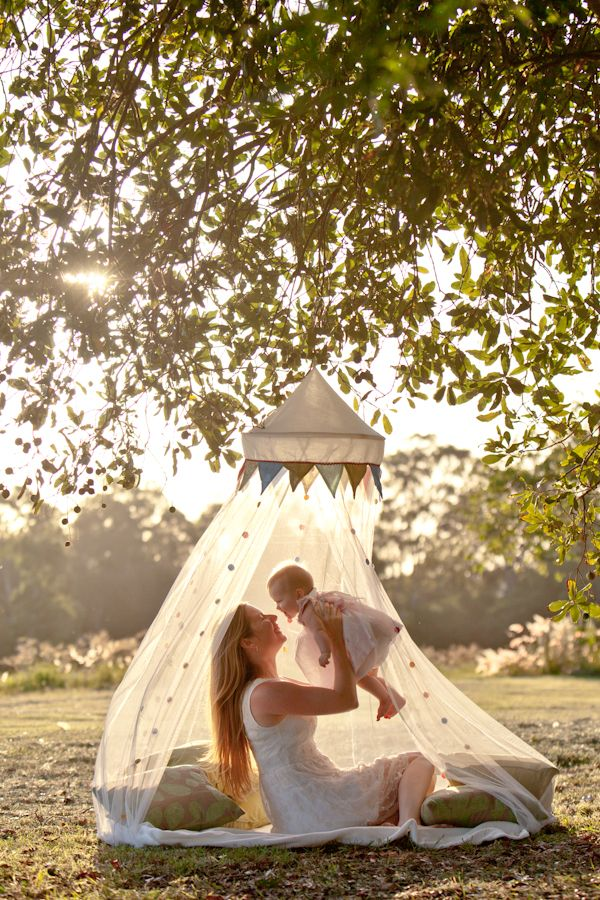 fancy mosquito net canopy hangs from tree above picnic blanket