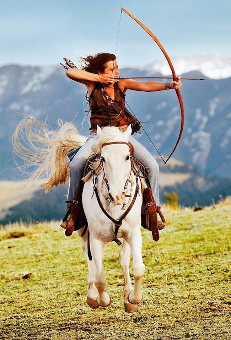 Horse running and lady shooting a bow and arrow from off his back. That take talent!