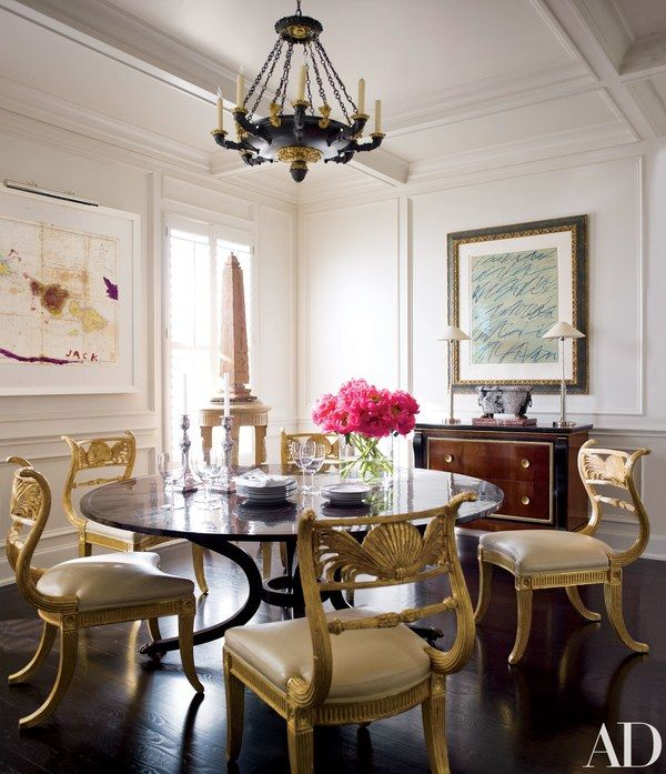 A mixed-media work by Julian Schnabel, left, and a lithograph by Twombly are mounted in the dining room. Powers improved the plain ceiling by raising it several inches and adding coffers. The Regency-style gilt-wood chairs, cushioned with Hermès leather, are by Rose Tarlow Melrose House. The table is by Dessin Fournir, and the commode, one of a pair, is Italian Empire.
