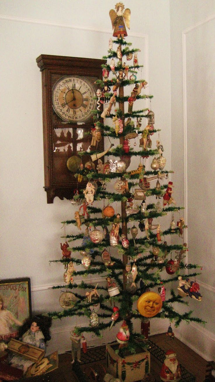 "Antique feather tree decorated with antique glass ,Dresden, and cotton ornaments. Antique Schoenhut ""Santa""  Rolly-Polly toy under tree."