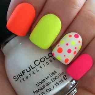 Llamativa manicura de uñas decorada con colores fluor en naranja, amarillo y rosa, una de ellas en color blanco con lunares de estos colores.