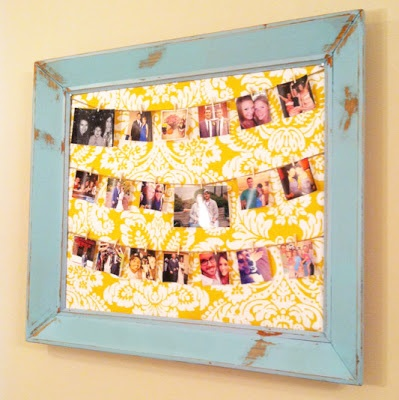 Old frame made to look rustic, fabric backing, and 3 rows of twine with pictures hung by mini clothes pins!