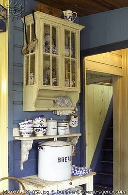 love the little glass wall cupboard & the shelf below ~ with that little table it could be a drink station in the kitchen or an enclosed porch ~ taverne-agency (via yhtuyt: August 2010)