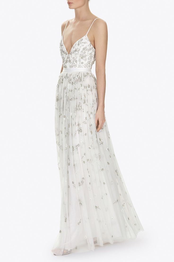 The Astral Maxi Dress features a delicate trailing floral motif in silver-cut beads and sequins, that catch the light as the dress moves for overall shimmering effect. The artwork begins at the bodice and floating petal motifs scatter down towards the hem, creating a flattering fairytale silhouette. The beautifully constructed dress is finished with a grosgrain trim, a delicate fitted bodice with fine adjustable straps and a ethereal open back, with delicate ribbon tie detail. The skirt is…