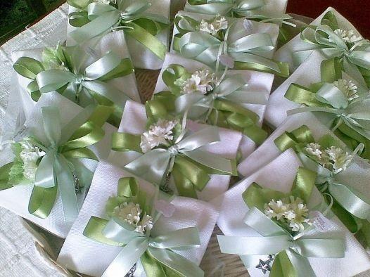 Fiocchi e fiori di raso per un'eleganza sussurrata ma dirompente per queste bomboniere matrimonio su toni verdi