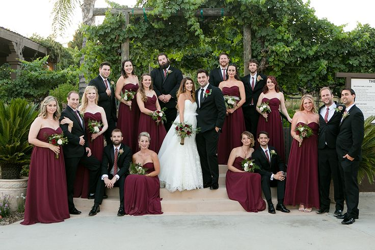 Temecula outdoor wedding at wilson creek winery bride strapless mermaid style gown with sweetheart neckline and lace detail with crystal necklace and bracelet with groom black notch lapel tuxedo with long black tie and red floral boutonniere with bridesmaids long burgundy dresses with groomsmen black tuxedo with long burgundy ties