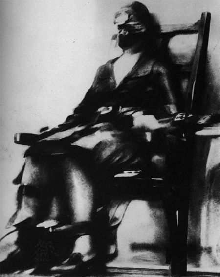 """Ruth Snyder at the moment of execution. """"On that fateful day  (12 Jan 1928), Tom Howard, posing as a writer, arrived early in Sing Sing Prison and took up a vantage position. A miniature camera was strapped to his left ankle, the shutter release button was concealed within his jacket. As Snyder's body shook from the jolt, Howard hoisted his pant leg and secretly snapped with a one-use camera."""""""