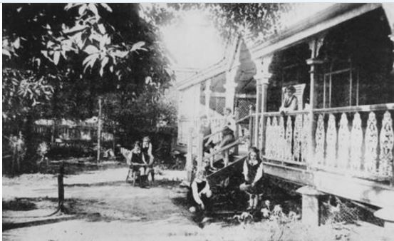 1928 Beresford House School, Bundaberg. School children in the front yard and on the steps of Beresford House School. The building is a classic Queenslander with a verandah at front which has vertical wrought iron railings. Beresford House School was a boarding and day school where boys and girls were prepared for the High School examinations. (Information taken from: Burnett & Isis Pictorial, c.1927)