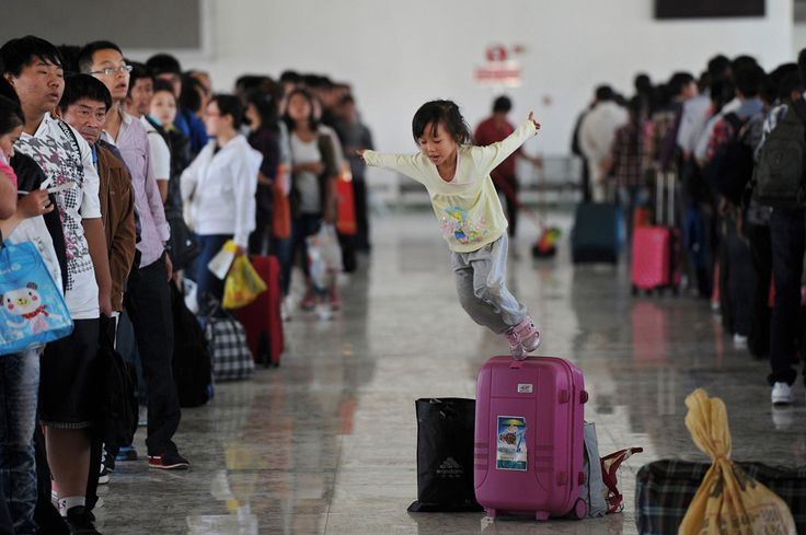 A girl jumps off a luggage box inside a waiting room of a long-distance bus station ahead of a national-wide eight day break for celebrating China's Mid-Autumn festival and National Day, in Hefei, Anhui province, Sept. 29, 2012. (Reuters)#