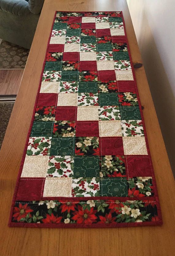 Quilted Christmas Table Runner measuring 16 x 48, created in traditional holiday colors of red, green, white, gold, with a black background. Fabrics feature poinsettia prints with coordinating themed Christmas fabrics. A traditional diagonal block pattern has been used in the