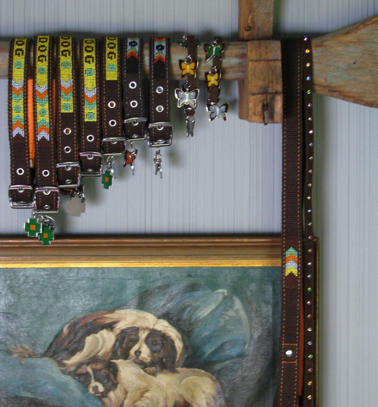 Easy display using an old canoe paddle and bracket. Easy to lift paddle off bracket to remove collars. Mix in dog art for fun.