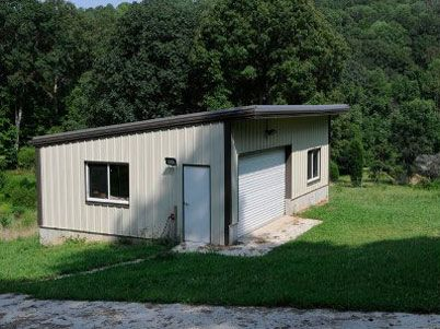 Single slope garage freedom steel steel buildings for Building a garage on a sloped lot