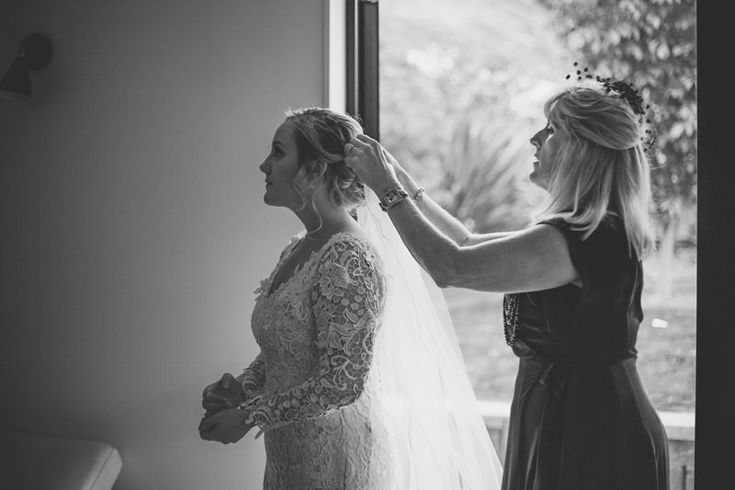 Bride getting ready at Arthurs Point accommodation in white lace gown for Queenstown wedding New Zealand.  Gown by Nicola Dawson Design