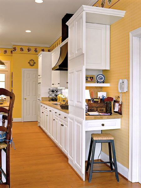 While including a home office is a definite trend today, not all kitchens are spacious enough for such an area. Here's a clever solution. A hidden nook houses a small desk, phone, and cabinet behind a false front of cabinets. (Photo: Photo: Laurey W. Glenn; Stylist: Lisa Powell)