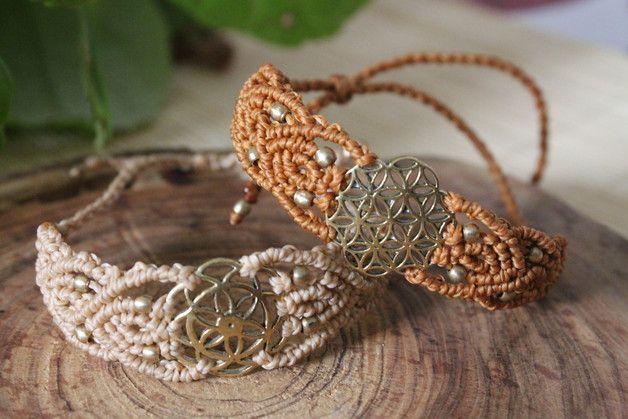 Pulseras en macramé hecho totalmente a mano con abalorios de bronce, en forma de flor de la vida y semilla de la vida y cuentas bronce. El cierre es con un nudo corredizo ajustable a la muñeca....
