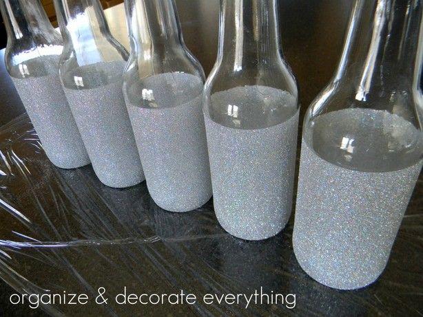 Fles eerst goed schoonmaken. Daarna met schilderstape afplakken tot waar je de glitter wil hebben. Inspuiten met mod podge en door de glitter rollen.. Even laten drogen en daarna voorzichtig de tape er af halen...!