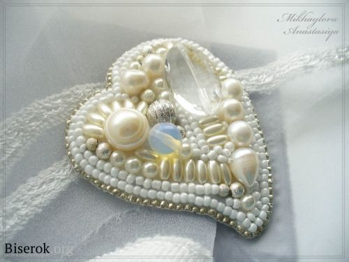 Witte broche in de vorm van hart  met veel plaatjes uitleg