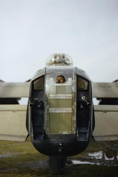 The rear gunner of a Lancaster of No. 44 Squadron peeks out through a cut-out in the perspex of his gun turret, October 1942. A gunner, bel...
