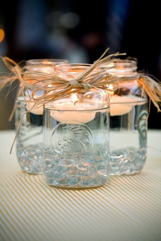 Mason jars filled with water, a decorative ribbon or string tied around the rim, with a long burning floating candle in each jar. Group 3-4 jars together for a beautiful centerpiece!